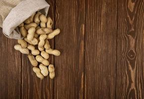 Draufsicht von Erdnüssen in der Schale, die von einem Sack auf hölzernem Hintergrund mit Kopienraum verstreut sind