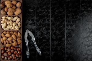 Draufsicht der Nussmischung Walnüsse Haselnüsse Mandel und Erdnüsse in der Schale mit Nussknacker auf schwarzem Hintergrund mit Kopienraum