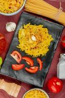 Draufsicht von Makkaroni-Nudeln und geschnittenen Tomaten in Platte mit verschiedenen Makkaronis als Fadennudeln und anderem Knoblauchsalz auf Bordo-Stoffhintergrund foto