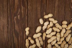 Draufsicht der Erdnüsse in der Schale verstreut auf hölzernem Hintergrund mit Kopienraum