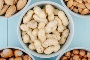 Draufsicht der Erdnuss in der Schale in einer Schüssel auf blauem Hintergrund