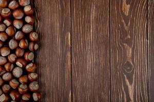 Draufsicht von Haselnüssen in der Schale verstreut auf hölzernem Hintergrund mit Kopienraum foto