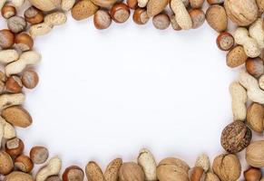 Draufsicht von gemischten Nüssen in der Schale Haselnüsse Erdnüsse Walnüsse und Mandel auf weißem Hintergrund mit Kopienraum foto