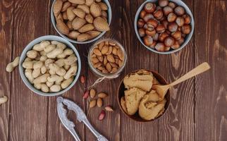 Draufsicht von gemischten Nüssen und einer Schüssel mit Erdnussbutter mit einem Nussknacker auf hölzernem Hintergrund
