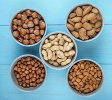 Draufsicht von gemischten Nüssen in der Schale und ohne Schale in Schalen Mandel-Haselnüssen und Erdnüssen auf blauem Hintergrund foto
