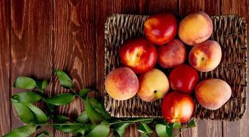 Draufsicht von Pfirsichen in Korbteller auf hölzernem Hintergrund verziert mit Blättern