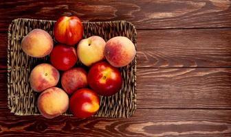 Draufsicht von Pfirsichen in Korbteller auf der linken Seite und hölzernem Hintergrund mit Kopienraum foto