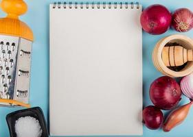 Draufsicht auf Zwiebeln mit Salz, schwarzen Pfeffersamen und Reibe um Notizblock auf blauem Hintergrund mit Kopienraum