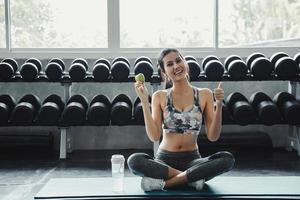 junge Frau sitzt auf Yogamatte