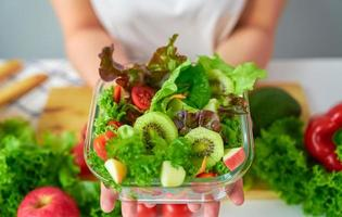 Frauenhände zeigen Salatschüssel