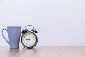 Tasse und Wecker auf dem Schreibtisch foto