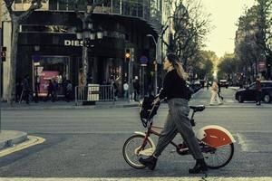 Frau, die mit einem Fahrrad in Barcelona, 2017 geht foto