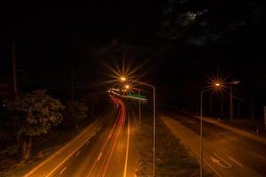 Straßenlaternen und Lichtspuren bei Nacht