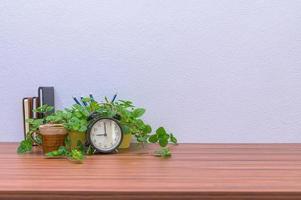 Blumen- und Wecker auf dem Schreibtisch