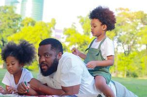 Familie glücklich, sich im Urlaub gemeinsam auf den Rasen im Park zu legen. Konzept der Liebe und familiären Bindungen