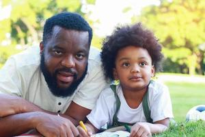 Vater und Sohn legen sich gerne im Urlaub auf den Rasen im Park. Konzept der Liebe und familiären Bindungen