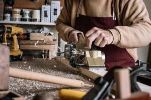 Zimmermann bearbeitet das Holz mit einer elektrischen Bürste