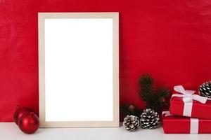 leere hölzerne Fotorahmen-Modellschablone und Weihnachtsdekoration auf rotem Hintergrund