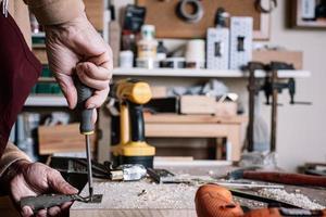 Zimmermann schraubt ein Scharnier mit einem Schraubendreher an ein Brett