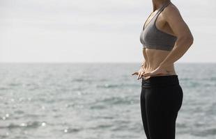 Frau macht hypopressive Übung im Meer