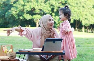 muslimische Mütter und Töchter genießen ihren Urlaub im Park. Liebe und Bindung zwischen Mutter und Kind foto