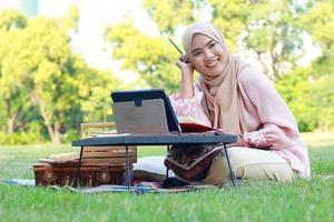 schönes muslimisches Mädchen, das glücklich im Park sitzt. muslimische Frau, die im Gartenrasen lächelt. Lebensstilkonzept einer selbstbewussten modernen Frau