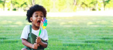 Porträt des Jungen, der freudig und glücklich im Sommer Windkraftanlage im Park spielt foto