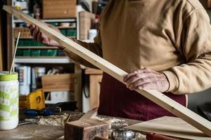 Zimmermann, der ein Holzbrett in einer Zimmerei betrachtet