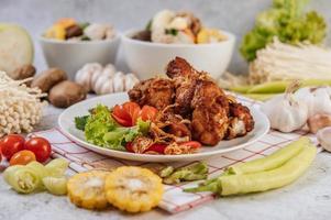 gebratene Hähnchenschenkel mit Tomaten, Chili, gebratenen Zwiebeln, Salat, Mais und Pilzen
