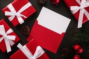leere weiße Grußkarte und Umschlagmodell mit Weihnachtsgeschenkdekorationen auf Schmutzhintergrund