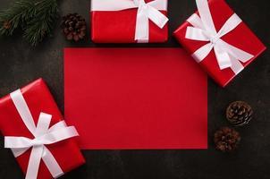 leeres rotes Grußkartenmodell mit Weihnachtsgeschenkdekorationen auf Schmutzhintergrund