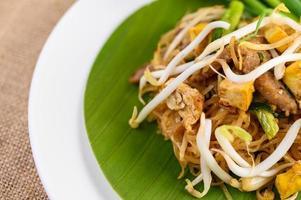 thailändisches Gewürz in einem weißen Löffel auf einem Holztisch