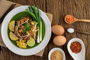 Pad Thai mit Zitrone, Eiern und Gewürzen auf einem Holztisch foto