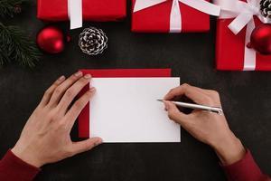 Hände, die weißes Grußkartenmodell mit Weihnachtsdekoration auf Schmutzhintergrund schreiben