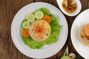 gebratener Reis auf einem weißen Teller mit Salat und Beilage