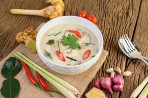 Tom Kha Kai, thailändische Kokosnusssuppe auf hölzernem Küchenbrett