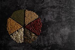 Hülsenfrüchte in einem Kreis auf einer schwarzen Zementoberfläche angeordnet foto