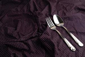 Löffel und Gabel auf ein zerknittertes Tuch gelegt