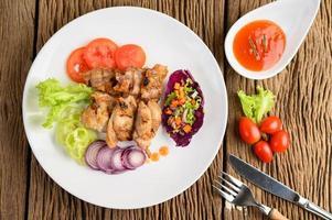 gegrilltes Hähnchen auf einem Holzschneidebrett mit Salat