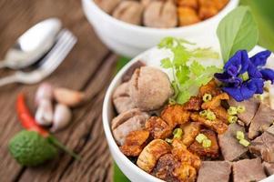 Nudeln in einer Schüssel mit knusprigem Schweinefleisch und Fleischbällchen