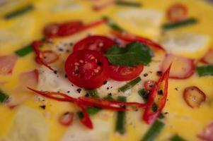 Nahaufnahme von gedämpften Eiern mit Speck, Chili und Frühlingszwiebeln