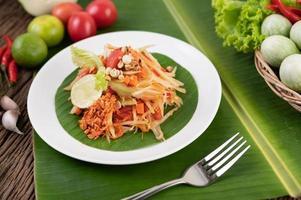 thailändischer Papayasalat mit Bananenblättern und frischen Zutaten foto
