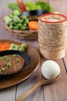 Chilipastenpaste in einer Schüssel mit Auberginen, Karotten, Chili und Gurken in einem Korb