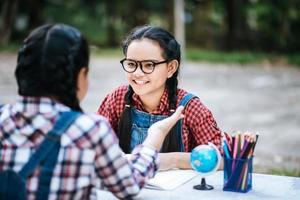 zwei Mädchen studieren und reden in einem Park miteinander foto
