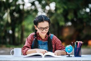 junges Mädchen, das draußen liest und denkt