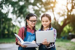 zwei Mädchen studieren und reden in einem Park miteinander
