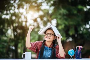 junges Mädchen mit Buch über dem Kopf im Park