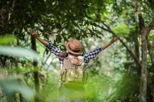 glückliche junge Frau, die ihre Arme hebt, um die Sonne im Wald zu begrüßen