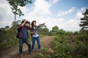 zwei junge Reisende mit Rucksäcken im grünen Dschungel