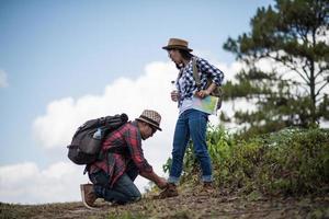 junger Mann, der Schuhe für Wandererin bindet